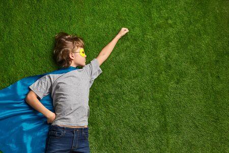 Little superhero flying against lawn Foto de archivo