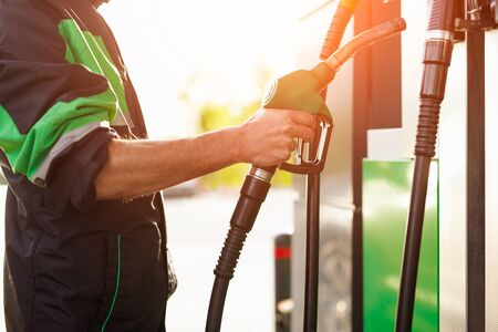 Crop employee taking nozzle from gas pump Stock Photo