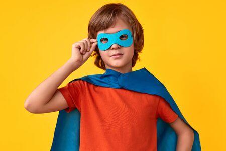 Confident superhero adjusting mask