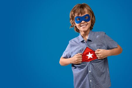 Cheerful boy showing superhero costume Banque d'images