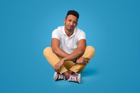 Relaxed black guy sitting with crossed legs