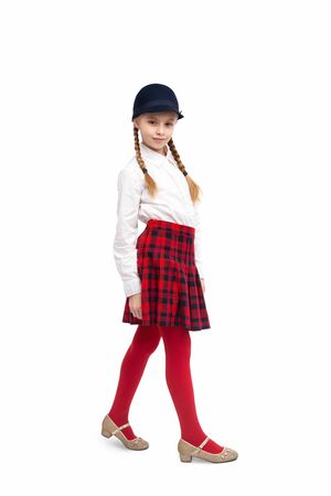 Schoolgirl in stylish hat looking at camera