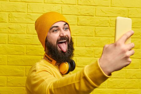 Funny man taking selfie near wall
