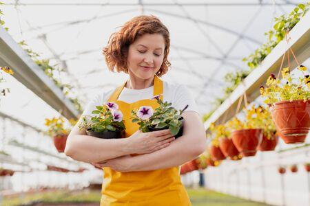 Vrouwelijke tuinman die ingemaakte bloemen omhelst