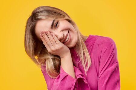 Cheerful young woman covering eye