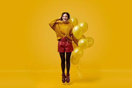 Weird female with balloons jumping and saluting