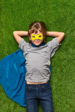 Confident superhero lying on lawn Foto de archivo