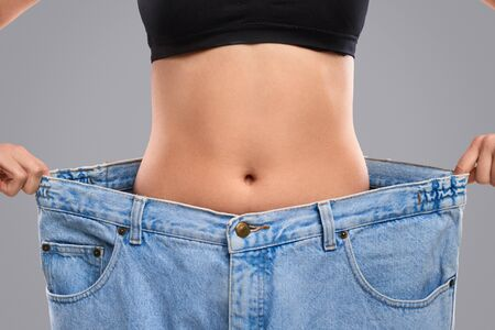 Dieting woman in oversized jeans