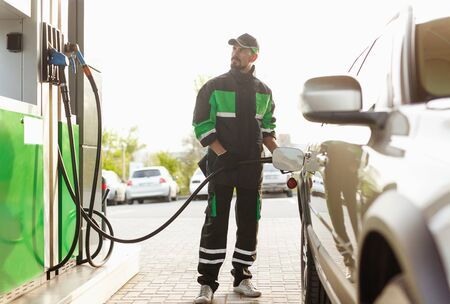 Gas station worker looking at pump Stock Photo
