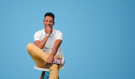 Positive black male sitting on chair
