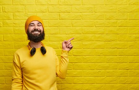 Happy bearded male stylish bright outfit smiling and pointing at empty space on yellow brick wall 스톡 콘텐츠