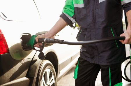 Crop worker filling vehicle with gas 版權商用圖片
