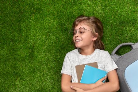 Smiling schoolboy lying on grass and looking away
