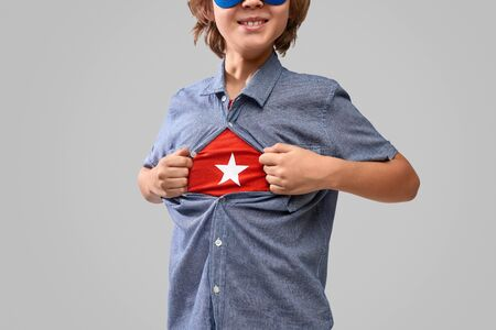 Crop boy revealing superhero emblem