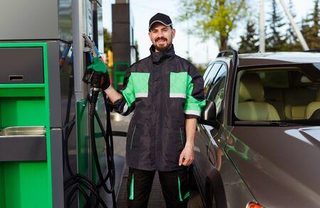 Smiling filling station worker with dispenser