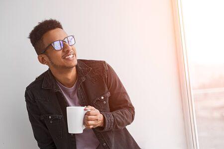 Cheerful black guy enjoying drink in morning