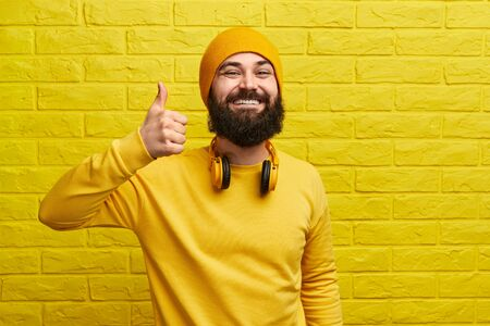 Smiling hipster gesturing thumb up near wall