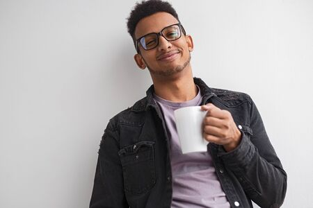 Pleased black man with hot beverage