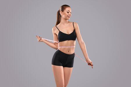 Mujer alegre envolviendo cinta métrica alrededor de la cintura