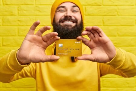 Credit card in hands of cheerful hipster