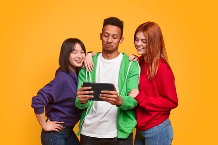 Multiethnic friends using tablet together Stock Photo