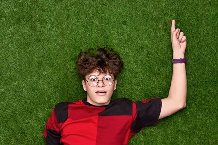 Amazed teen boy pointing up on grass Stockfoto