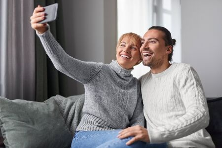 Happy couple taking selfie at home