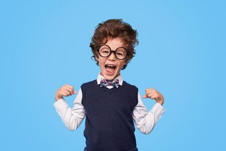Excited schoolboy looking at camera
