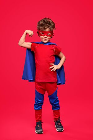 Little superhero showing biceps