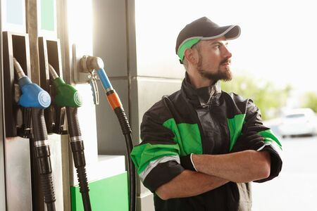 Confident filling station employee looking away