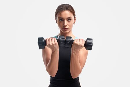 Athletic female exercising with dumbbells