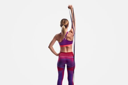 Unrecognizable athletic woman exercising with resistance band