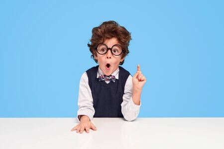 Surprised schoolboy sitting at desk