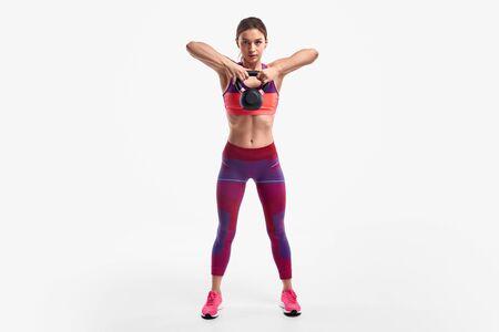 Strong woman lifting kettlebell up