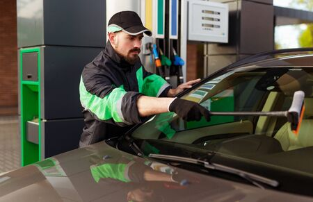 Bearded man washing windscreen of modern car