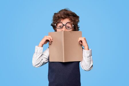 Funny schoolboy with notebook