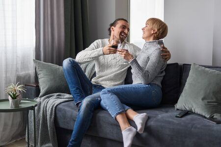 Couple laughing and drinking wine at home