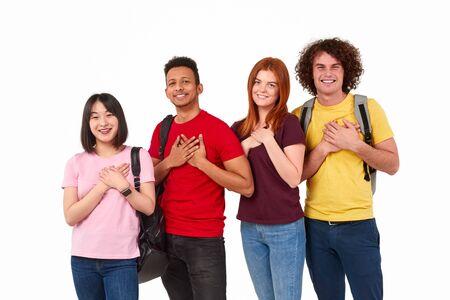 Kind multiethnic people keeping hands near heart