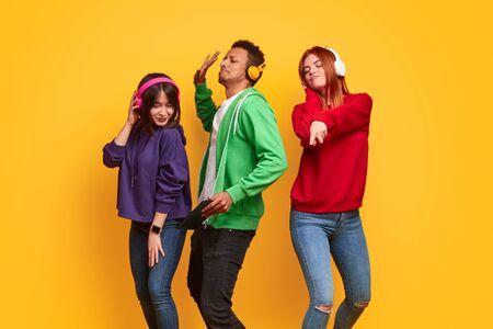 Mutliethnic friends in headphones dancing 版權商用圖片