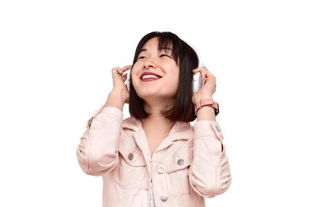 Cheerful Asian female listening to music