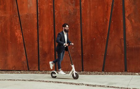 Cheerful businessman riding electric scooter Imagens