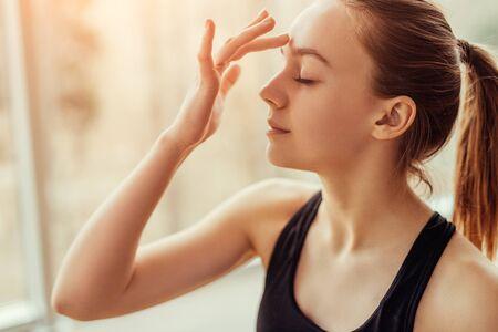 Young woman massaging third eye chakra Banque d'images