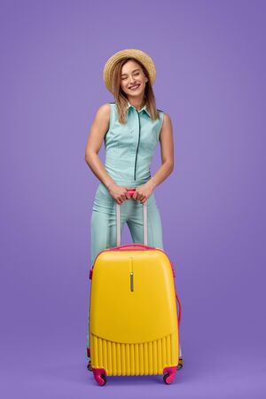 Laughing female traveler with luggage