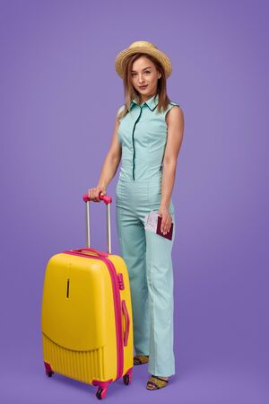 Confident traveler standing with luggage