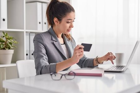 Young woman entering credit card credentials for online purchase