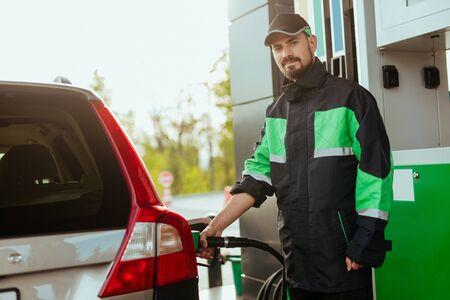 Benzinestation werknemer camera kijken Stockfoto