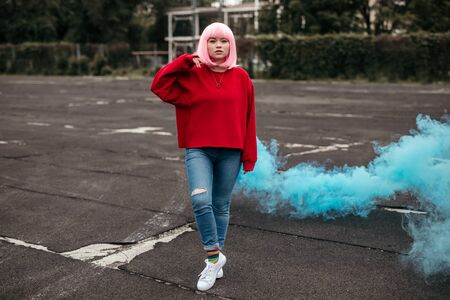 Female hipster with blue smoke bomb on street