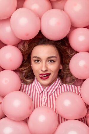 Mujer elegante en globos mostrando lengua