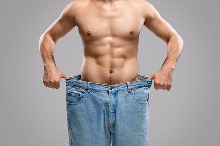 Hombre de cultivo que muestra el progreso de la pérdida de peso