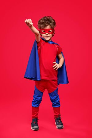 Little superhero in heroic pose